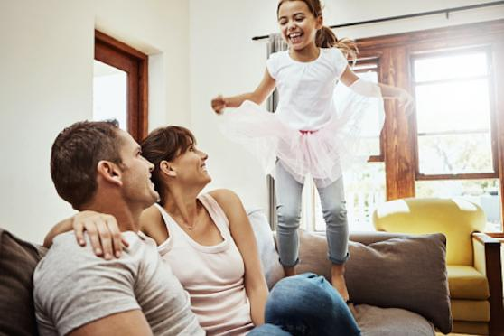 Young girl jumping on couch while parents watch.